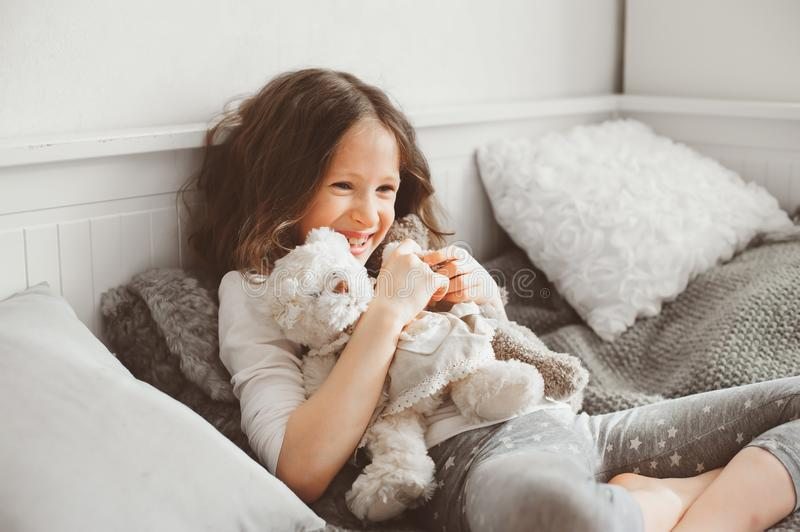 Happy kid girl playing with teddy bears in her room, sitting on bed. In pajama stock images