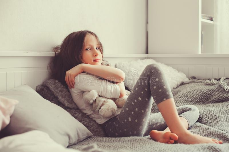 Happy kid girl playing with teddy bears in her room, sitting on bed. In pajama stock photos