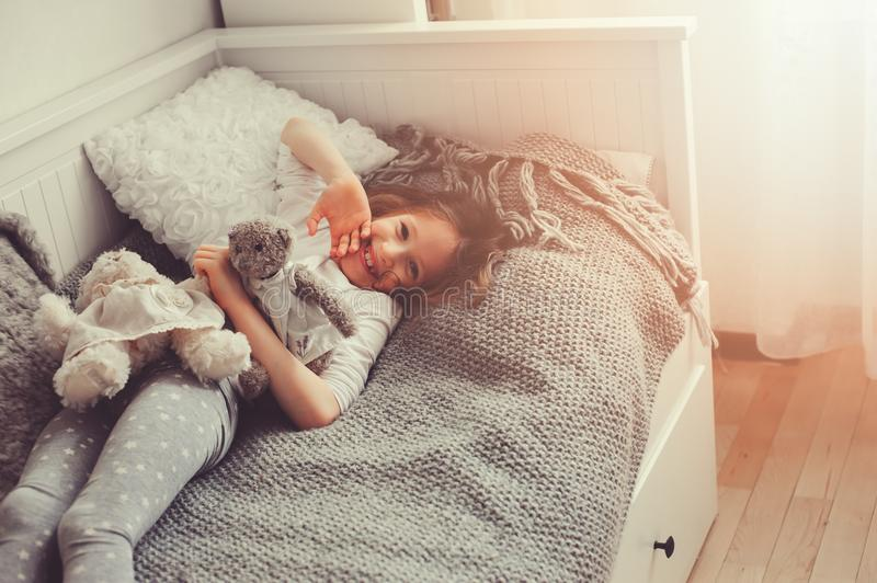 Happy kid girl playing with teddy bears in her room, sitting on bed. In pajama royalty free stock image