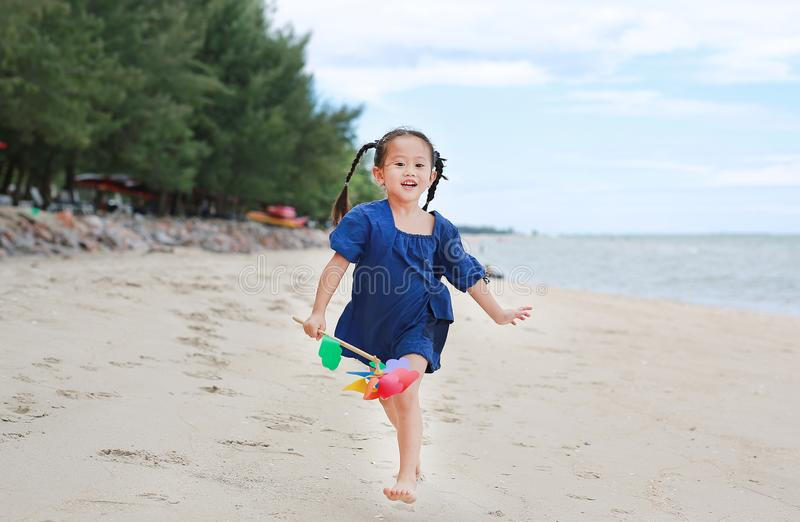 Happy kid girl running on the beach with holding a pinwheel in her hand royalty free stock images