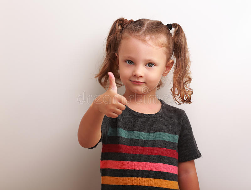 Happy kid girl showing thumb up sign stock photography