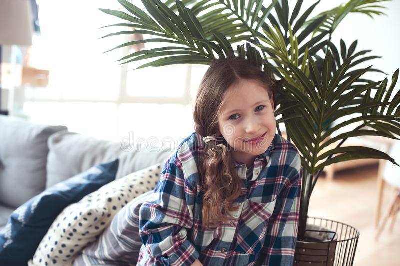 happy kid girl sitting on couch near tropical house plant stock images