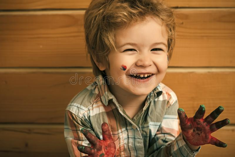 Happy kid having fun. Boy artist happy smiling on wooden wall royalty free stock photo