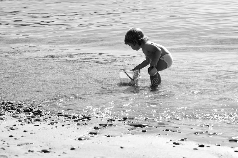 Happy kid having fun. Boy playing on beach. Happy kid having fun. Childhood. Small curious funny blonde child boy standing on sea coast beach with wavy water royalty free stock images