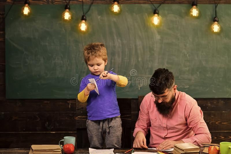 Happy kid having fun. Family leisure activity. Father and cute son making paper planes. Developing kids creativity stock photo