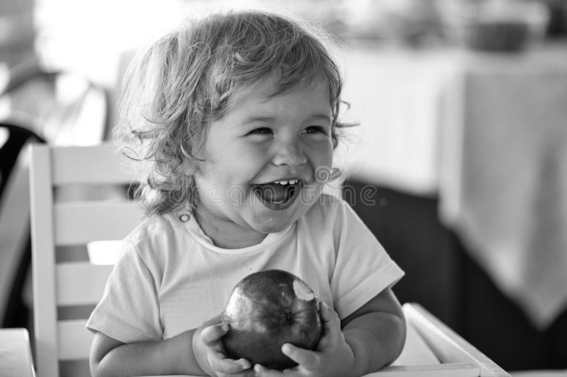 Happy kid having fun. Laughing baby boy with apple. Happy kid having fun. Laughing cute fair-haired blond hazel-eyed kid little child baby boy sitting in stock image