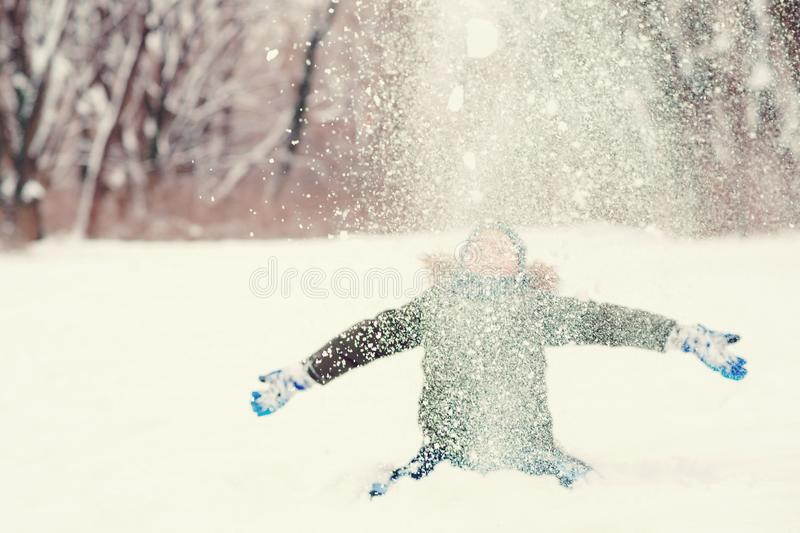 Happy kid having fun playing in the snow. Cute boy is throwing snow, enjoing snowy weather. Happy winter and christmas holidays. Winter fashion stock image