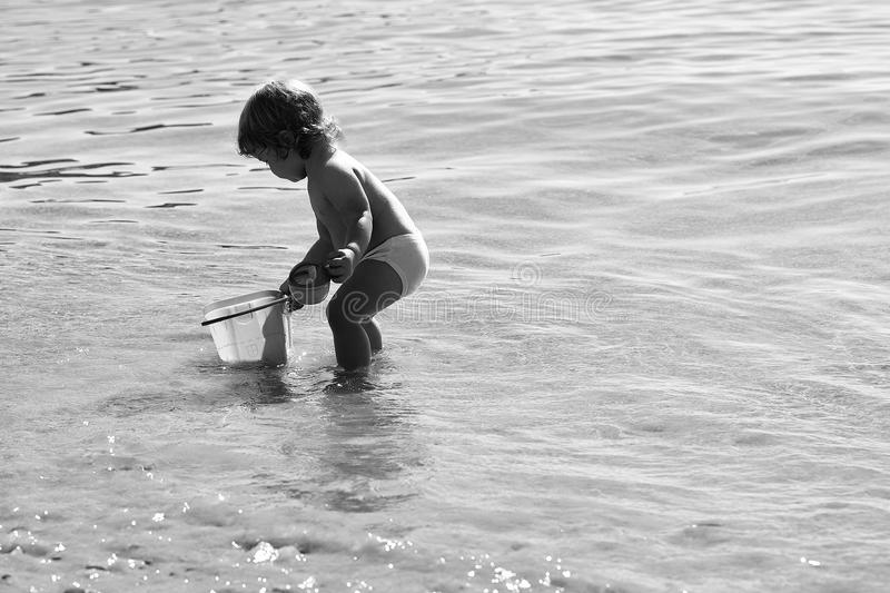 Happy kid having fun. Boy playing on beach. Happy kid having fun. Small curious funny blonde child boy standing on sea coast beach with wavy water sunny day royalty free stock photography
