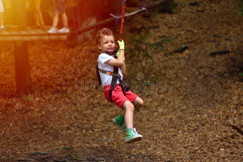 Happy kid with helmet and harness on zip line between trees stock photos