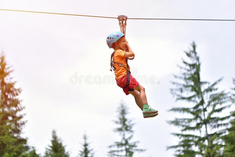 Happy kid with helmet and harness on zip line between trees stock photography