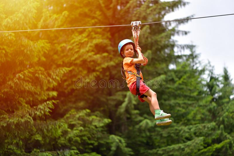 Happy kid with helmet and harness on zip line between trees royalty free stock images