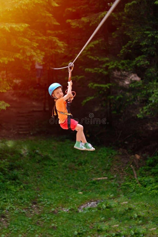 Happy kid with helmet and harness on zip line between trees stock images