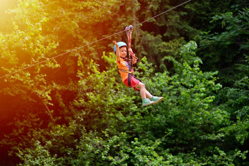 Happy kid with helmet and harness on zip line between trees royalty free stock photo