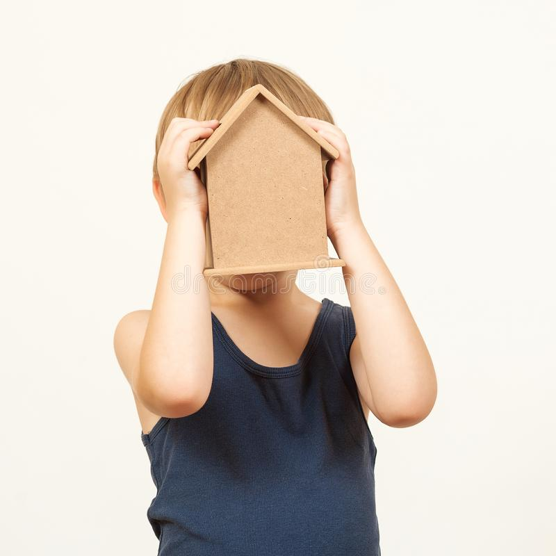 Happy kid hid his face behind small house toy. Dreaming about own home. Child playing with house toy. Real estate business concept stock photography