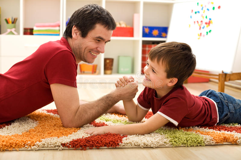 Happy kid and his father arm wrestling. Happy boy and his father arm wrestling laying on the floor in the kids room stock images