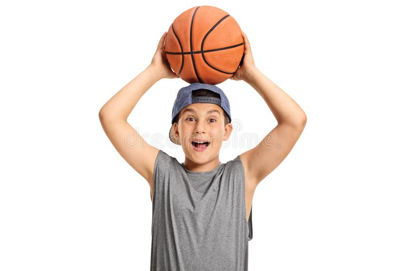 Happy kid holding a basketball and looking at the camera royalty free stock images