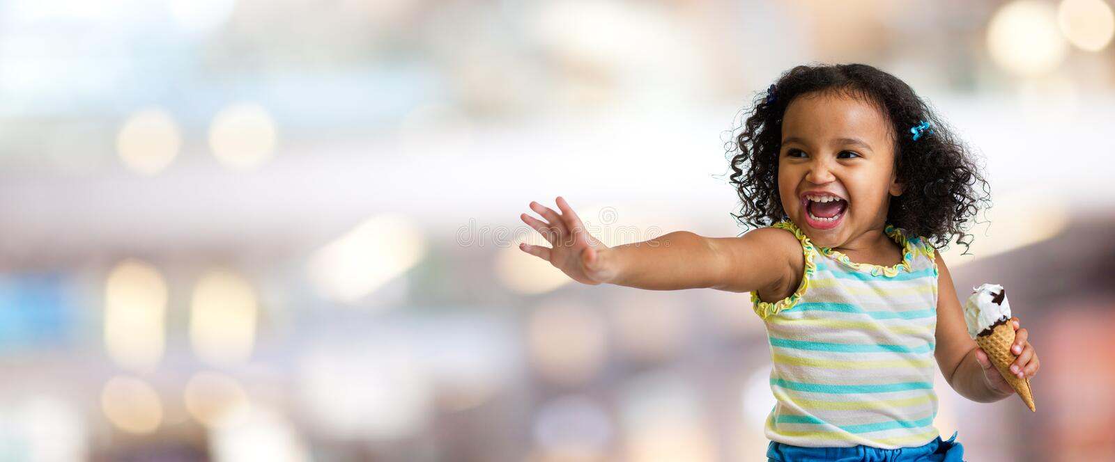 Happy kid with ice cream on blurred abstract background royalty free stock image