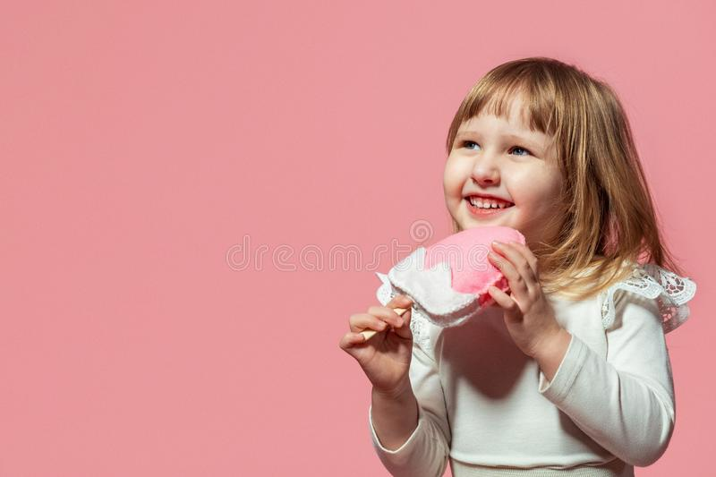 Happy kid with ice cream ice cream in hand on a pink coral background. royalty free stock photography