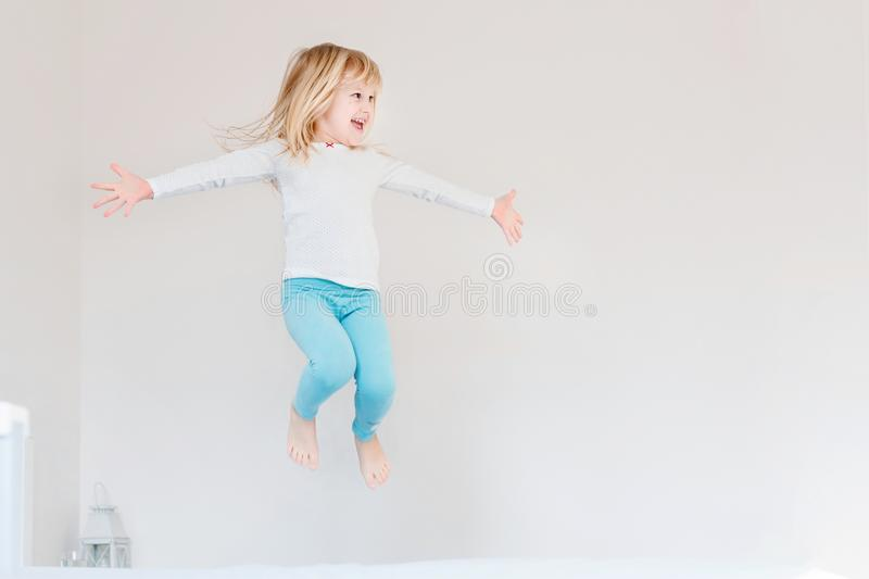 Happy kid jumping over bed. Cute little blond girl having fun indoors. Happy and careless childhood concept stock photo