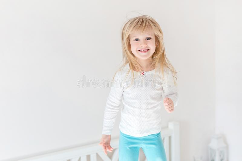 Happy kid jumping over bed. Cute little blond girl having fun indoors. Happy and careless childhood concept stock image