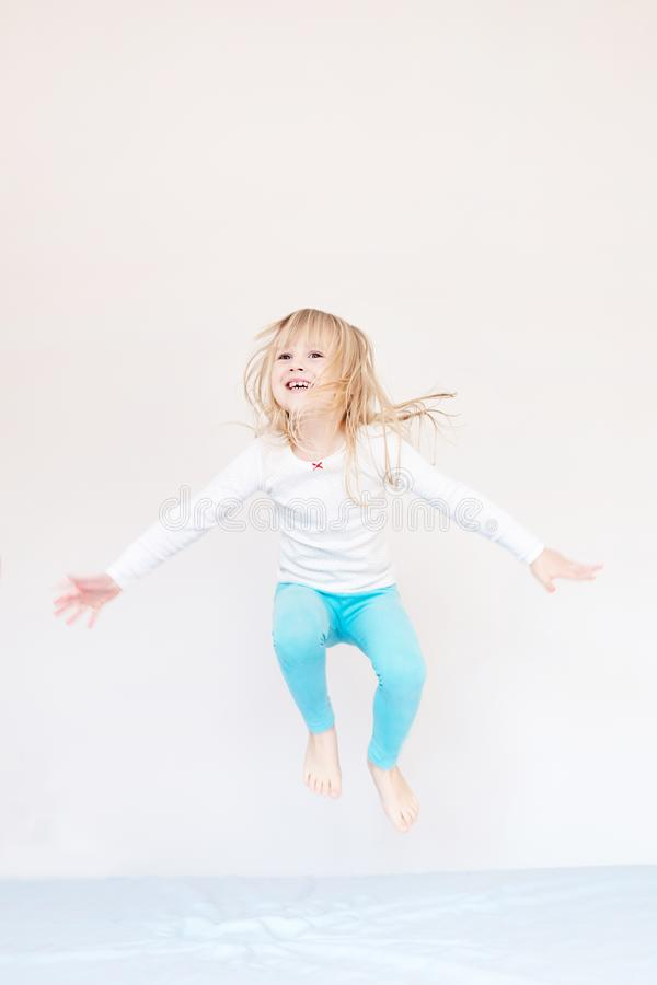 Happy kid jumping over bed. Cute little blond girl having fun indoors. Happy and careless childhood concept stock images