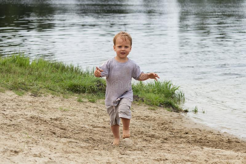 Happy kid at lake coast, running in the wet clothes on the sand and smiling. royalty free stock images