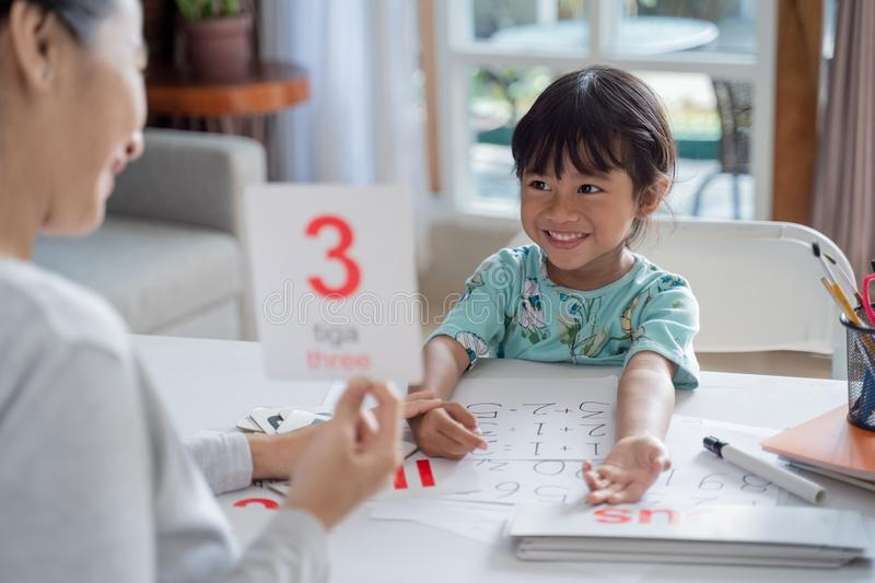 Happy kid learning and studying together with parent at home stock photography