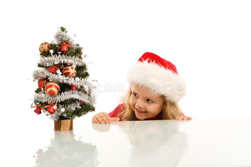 Happy kid lurking around a small christmas tree. Happy kid with santa hat lurking around a small christmas tree - isolated royalty free stock photos