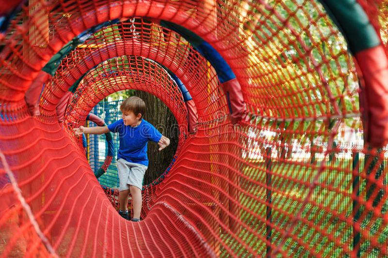 Happy kid at modern rope adventure park. Happy childhood. Summer holidays concept royalty free stock photos