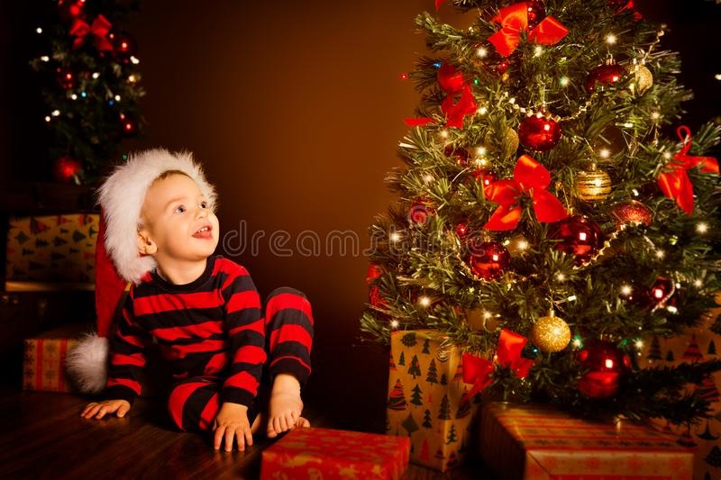 Happy Kid near Christmas Tree, Happy Baby Boy in Night Xmas Room, Child in Red Santa Hat, Present gift box. Happy Kid near Christmas Tree, Happy Baby Boy in royalty free stock photography