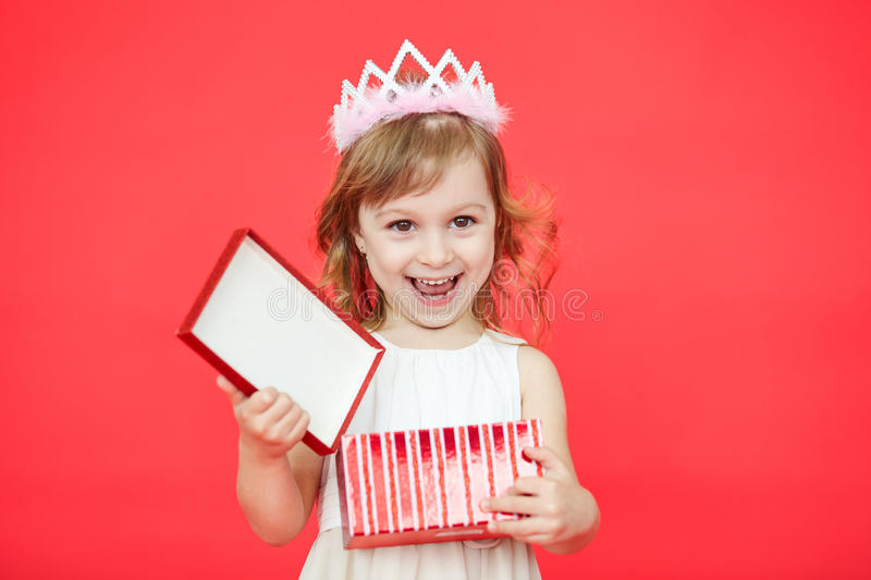Happy Kid opening a Gift Box on red background royalty free stock photos