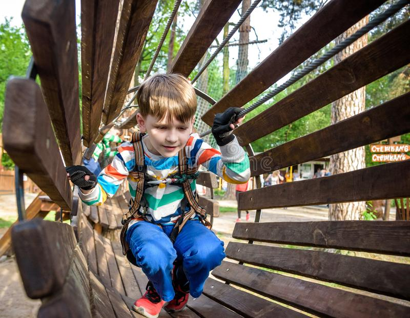 Happy kid overcomes obstacles in rope adventure park. Summer holidays concept. Little boy playing at rope adventure park. Modern royalty free stock photos
