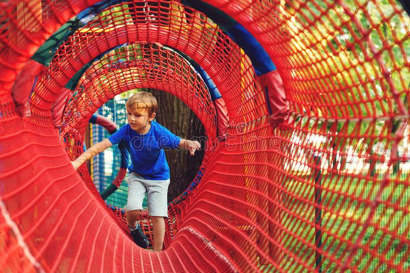 Happy kid overcomes obstacles in rope adventure park. Summer holidays concept. Little boy playing at rope adventure park. Modern royalty free stock images