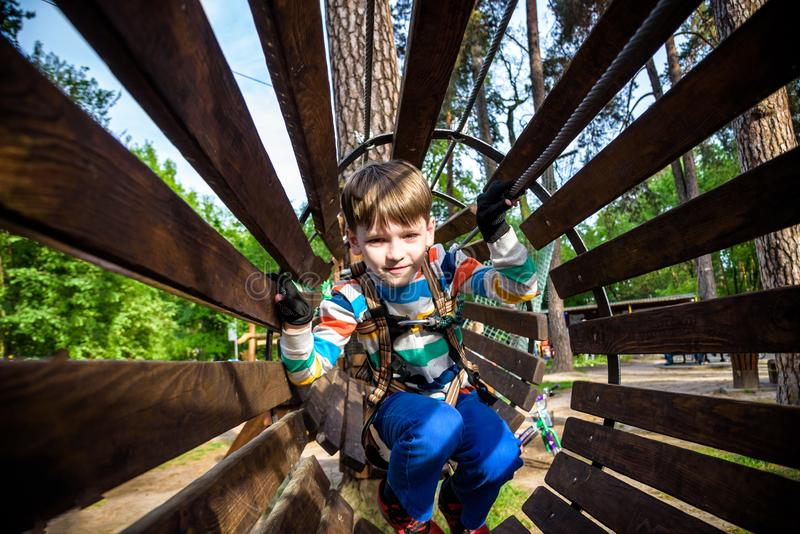 Happy kid overcomes obstacles in rope adventure park. Summer holidays concept. Little boy playing at rope adventure park. Modern royalty free stock photography