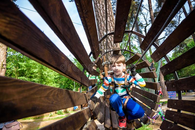 Happy kid overcomes obstacles in rope adventure park. Summer holidays concept. Little boy playing at rope adventure park. Modern stock images