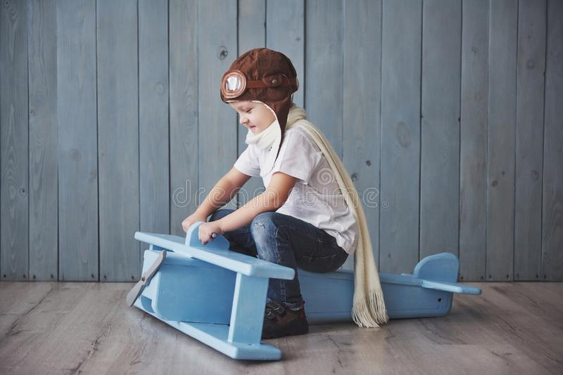 Happy kid in pilot hat playing with wooden airplane against. Childhood. Fantasy, imagination. Holiday royalty free stock photos