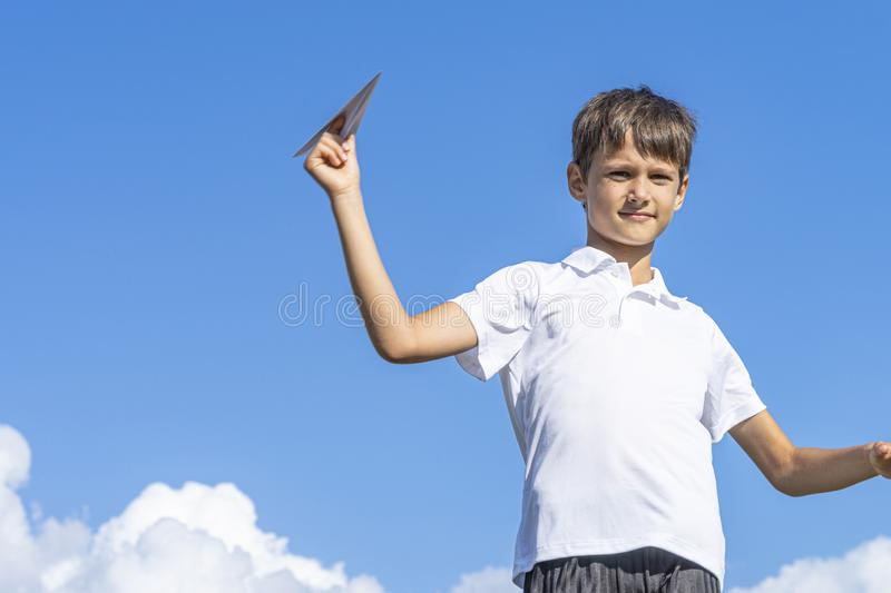 Happy kid playing with paper airplane against blue summer sky background royalty free stock photos