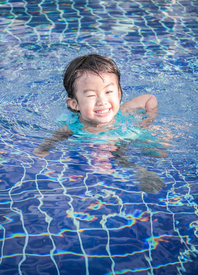 Happy kid playing in the swimming pool. Happy asian kid smile while playing in the swimming pool stock photos
