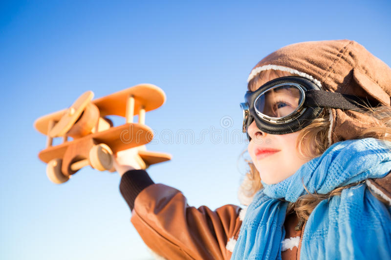 Happy kid playing with toy airplane. Against blue sky background royalty free stock photography