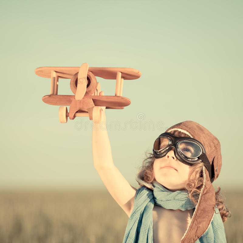 Happy kid playing with toy airplane. Against blue summer sky background royalty free stock images