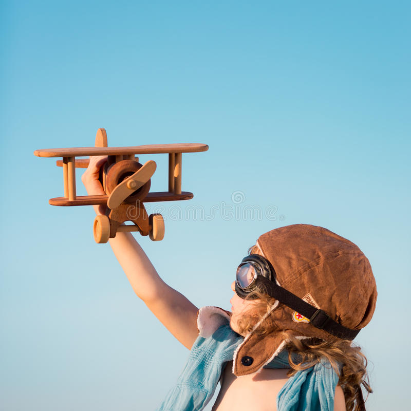 Happy kid playing with toy airplane. Against blue summer sky background stock photography