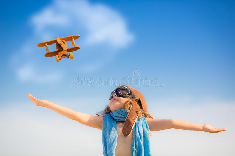 Happy kid playing with toy airplane. Against blue summer sky background royalty free stock photos