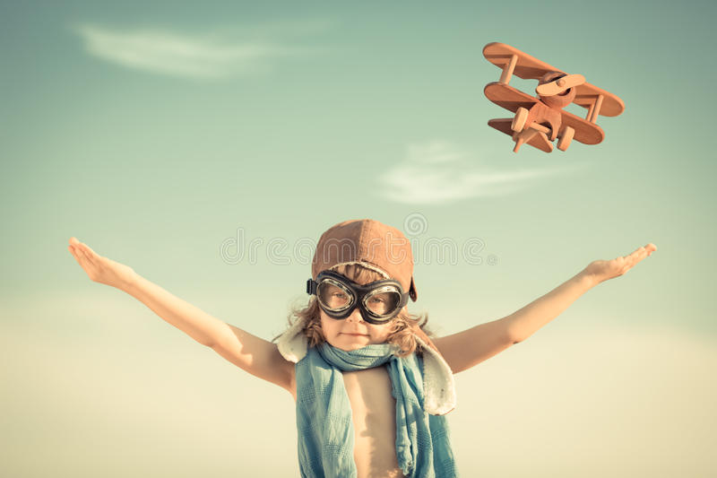 Happy kid playing with toy airplane. Against blue summer sky background. Vintage toned stock image