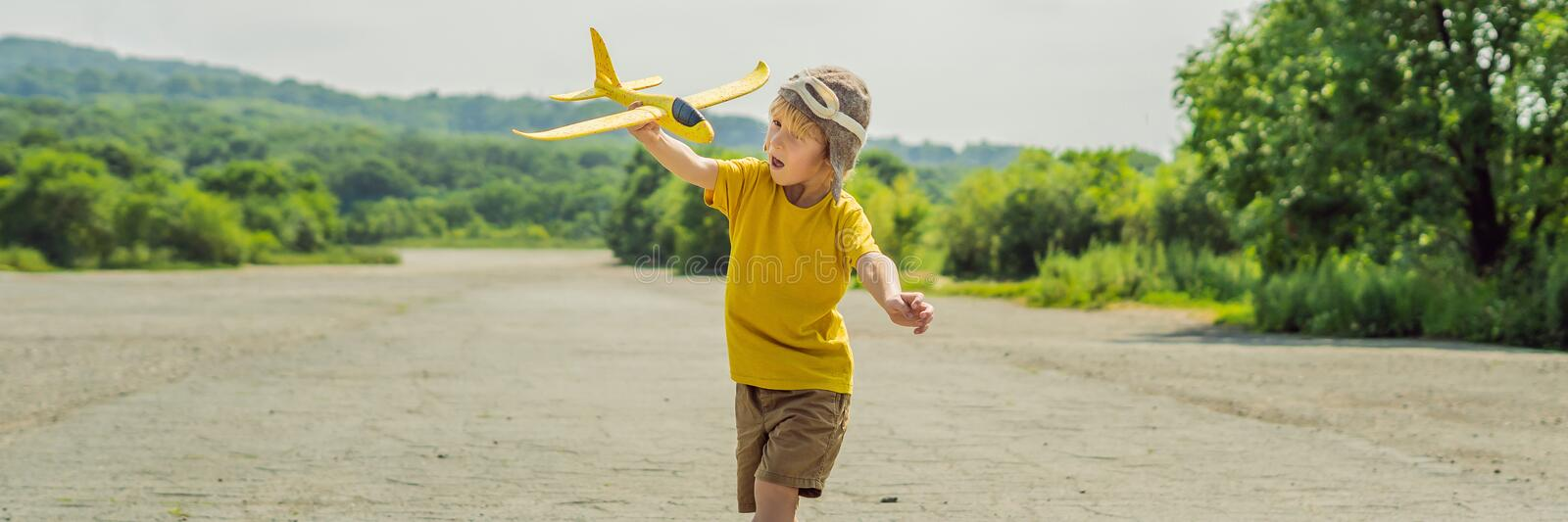 Happy kid playing with toy airplane against old runway background. Traveling with kids concept BANNER, LONG FORMAT. Happy kid playing with toy airplane against stock image