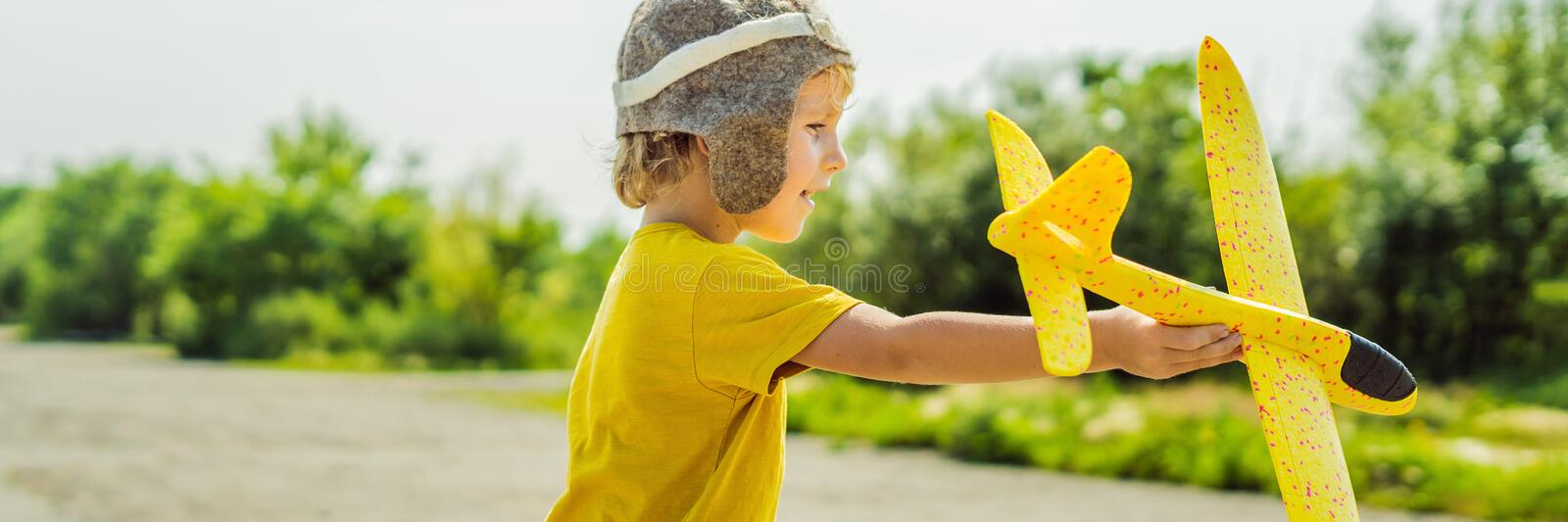 Happy kid playing with toy airplane against old runway background. Traveling with kids concept BANNER, LONG FORMAT. Happy kid playing with toy airplane against stock photo