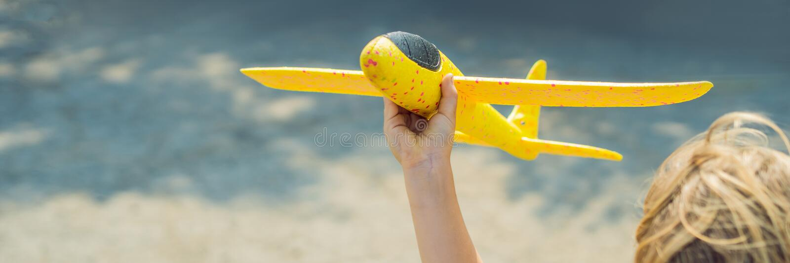 Happy kid playing with toy airplane against old runway background. Traveling with kids concept BANNER, LONG FORMAT royalty free stock photography