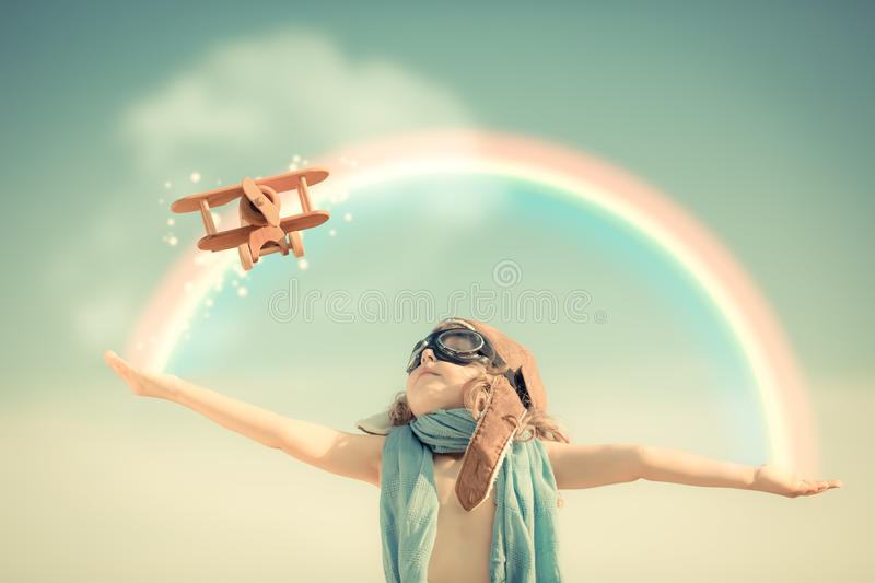 Happy kid playing with toy airplane. Against summer sky background royalty free stock image
