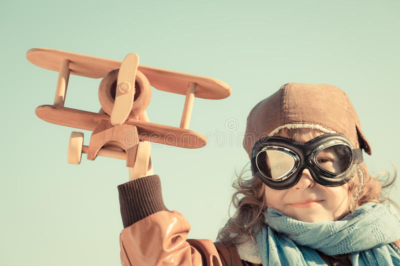 Happy kid playing with toy airplane. Happy kid playing with wooden toy airplane in autumn stock image