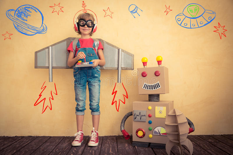 Happy kid playing with toy robot. At home. Innovation technology and success concept stock photography