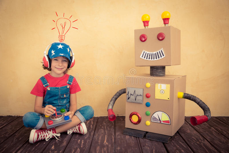 Happy kid playing with toy robot royalty free stock photo
